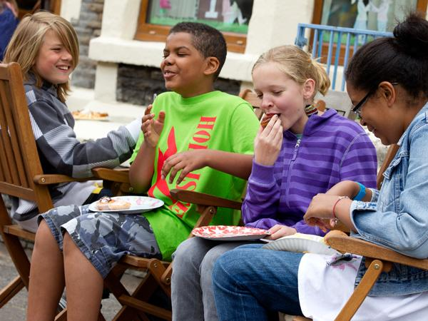Kids eating off paper plates in the street at a community Big Lunch
