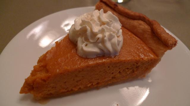 Slice of pumpkin pie with cream on top