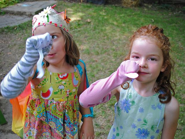 Girls dressed up in a garden holding sock puppets