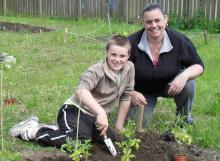 Mother and son sat on the grass planting tomatoes