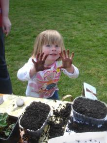 Child with muddy hands planting